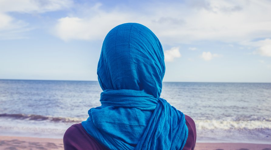 Kvinne med blå slør på hode, som står på en strand å ser ut over havet